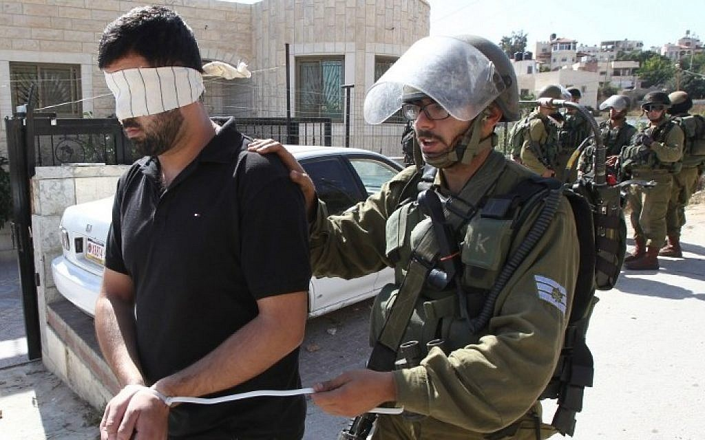Illustrative: Israeli security forces arrest and blindfold a Palestinian man during clashes in the village of Beit Omar, near the city of Hebron in the West Bank, on October 11, 2015. (AFP/Hazem Bader)
