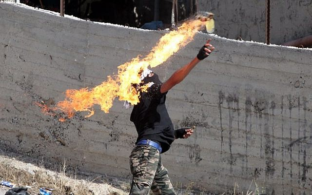 Illustrative: A Palestinian hurls a Molotov cocktail toward Israeli security forces during clashes, near the city of Hebron, in the West Bank, on October 11, 2015. (AFP/Hazem Bader)
