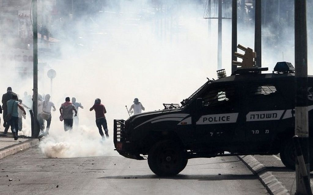 An Israeli police vehicle drives in front of Palestinian protesters running away during clashes on October 13, 2015 in the West Bank city of Bethlehem. (AFP/MUSA AL-SHAER)