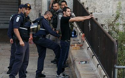 An Israeli policeman checks a young Palestinian man at the Damascus Gate entrance to the Old City of Jerusalem on October 13, 2015 as security measures are increased. (AFP PHOTO/AHMAD GHARABLI)