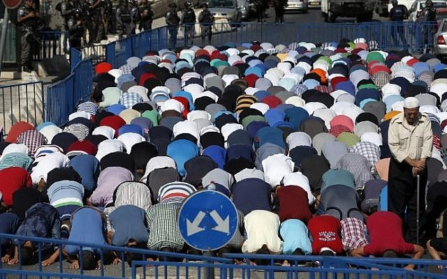 Israeli security forces stand guard as Palestinian Muslim worshipers take part in Friday noon prayers in the Ras al-Amud neighborhood in East Jerusalem, on October 16, 2015, following Israeli restrictions on the Temple Mount. (AFP/ AHMAD GHARABLI)