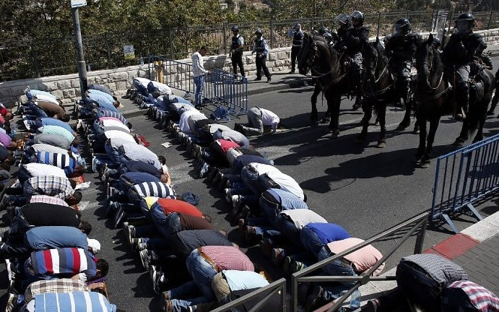 Israeli police stand guard as Palestinian Muslims pray on the streets of the Wadi al-Joz neighborhood in East Jerusalem during the Friday prayers following restrictions by Israeli police preventing Palestinians under 40 years old from entering the Temple Mount, on October 16, 2015. (AFP PHOTO / THOMAS COEX)