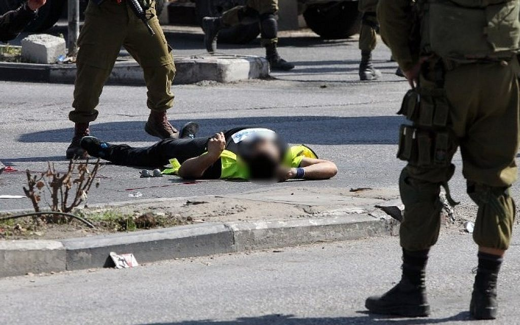 Israeli security forces stand next to the body of a Palestinian man disguised as a news photographer who carried out a stabbing attack against a soldier at the entrance to the city of Hebron on October 16, 2015 (Hazem Bader/AFP)