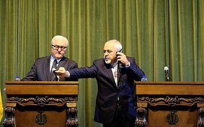 Iranian Foreign Minister Mohammad Javad Zarif (R) adjusts the microphone for his German counterpart Frank-Walter Steinmeier during a joint press conference in Tehran on October 17, 2015. (AFP PHOTO/ATTA KENARE)