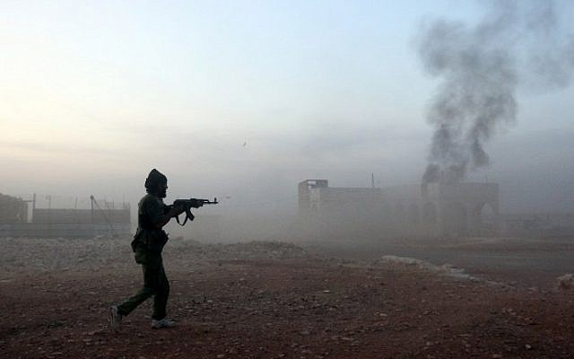 A picture taken on October 17, 2015 shows smoke billowing as a Syrian opposition fighter fires a weapon in the Mount Azzan area, 24 kms from the northern Syrian city of Aleppo, during reported fighting against forces loyal to Syrian President Bashar Assad. (AFP PHOTO/THAER MOHAMMED)