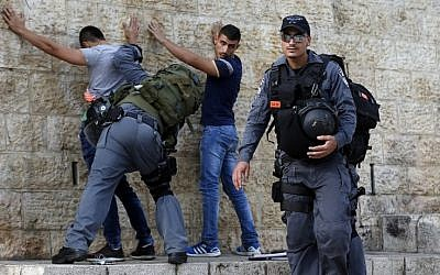 Israeli policemen check Palestinian youths at Damascus Gate in the Old City of Jerusalem on October 18, 2015. (AFP/Ahmad Gharabli)