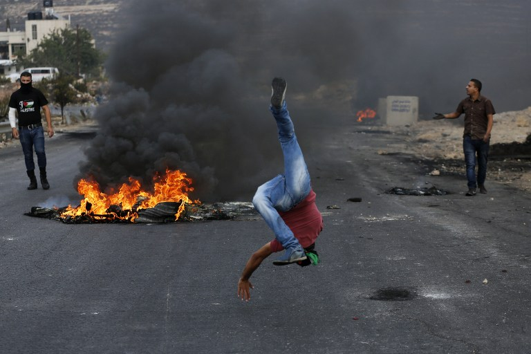 A Palestinian protester taunts Israeli border police during clashes next to the Jewish settlement of Beit El, north of Ramallah on October 19, 2015. (AFP/ABBAS MOMANI)