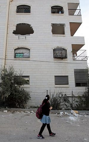 A Palestinian schoolgirl walks past a building housing the apartment of Maher al-Hashlamoun after its interior was destroyed by Israeli troops in the West Bank city of Hebron on October 20,2015. (AFP PHOTO/HAZEM BADER