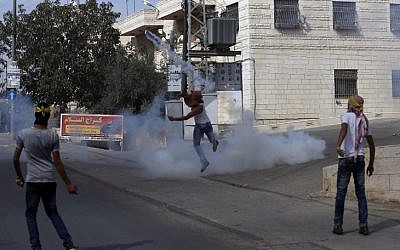 Masked Palestinian youth throw teargas back at Israeli border policemen during clashes in the Palestinian village of al-Ram, between Jerusalem and Ramallah in the West Bank, on October 22, 2015. (AFP PHOTO/ABBAS MOMANI)