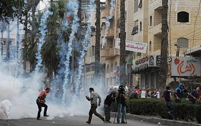 Palestinian stone throwers and journalists take cover from tear gas fired by Israeli security forces during clashes following Friday prayers on October 23, 2015, in the West Bank town of Hebron (Hazem Bader/AFP)