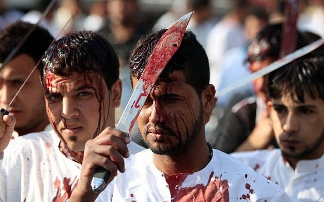 Iraqi men take part in a self-flagellation procession on the tenth day of the mourning period of Muharram, which marks the day of Ashura on October 24, 2015, in Baghdad's northern district of Kadhimiya. (AFP PHOTO/AHMAD AL-RUBAYE)