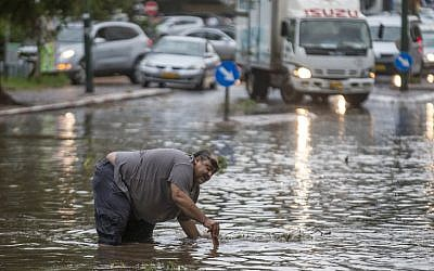 A Israeli man tries to open a sewer drain as water floods a street during a storm in Netanya, north of Tel Aviv on October 25, 2015. (AFP/JACK GUEZ)