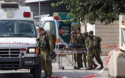 Israeli soldiers evacuate, on a stretcher, the body of Palestinian Raed Jarradat, who had stabbed and seriously wounded a soldier before he was shot dead, on Monday, October 26, 2015, near the West Bank city of Hebron (AFP PHOTO/HAZEM BADER)