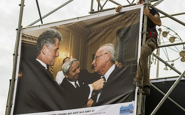 A worker hangs a picture taken by Israeli Government Press Office photographer Avi Ohayon showing former US president Bill Clinton arranging the tie of late Israeli prime minister Yitzhak Rabin along with Rabin's adviser Eitan Haber (L), displayed at an exhibition marking the 20th anniversary of Rabin's assassination, on October 26, 2015 in Tel Aviv. (AFP PHOTO/JACK GUEZ)