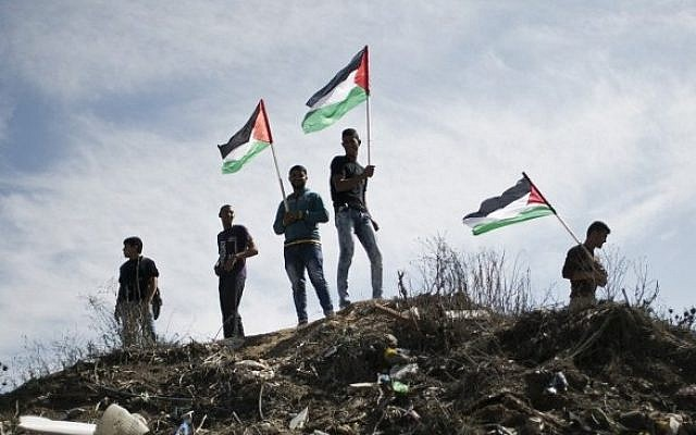 Palestinian demonstrators wave their flag during an anti-Israel protest east of Khan Younis, in the southern Gaza Strip, near a border fence with Israel, on October 28, 2015. (Said Khatib/AFP)