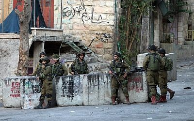 IDF soldiers stand guard near the site where a Palestinian attempted to stab a soldier before being shot dead in the West Bank city of Hebron on October 28, 2015. (AFP/Hazem Bader)