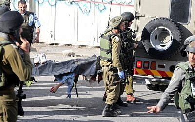 Israeli security forces carry the body of a Palestinian man who stabbed and wounded an IDF soldier before being shot dead by a Border Police officer in Hebron on October 29, 2015. (AFP/HAZEM BADER)