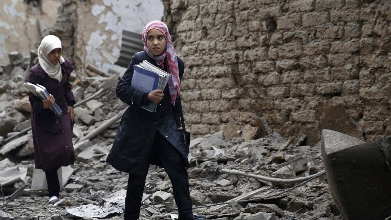 Syrian young women carry books as they walk amid the rubble of destroyed buildings following a reported air strike by Syrian government forces in the rebel-held area of Douma, east of the capital Damascus, on October 29, 2015. (Sameer al-Doumy/AFP)