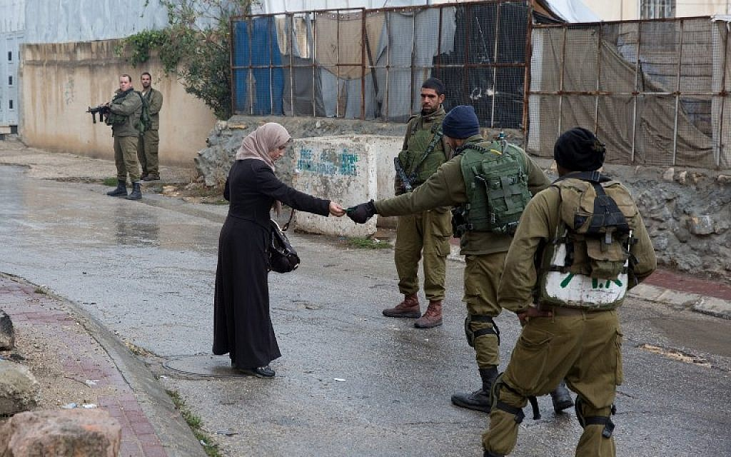 Illustrative: Israeli soldiers check the ID of a Palestinian woman near a Jewish enclave in Hebron on October 29, 2015. (AFP/Menahem Kahana)