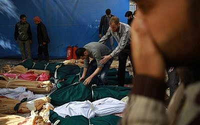 Syrian men try to identify the bodies of loved ones following a reported airstrike by Syrian government forces on the rebel-held town of Douma, on the eastern edges of the capital Damascus, on October 30, 2015. (AFP/ ABD DOUMANY)
