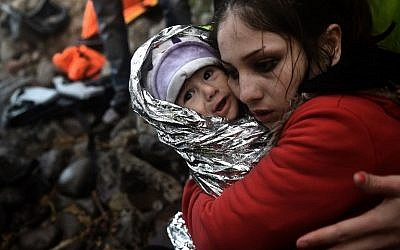 A woman hugs a baby wrapped in an emergency blanket as refugees and migrants arrive on the Greek island of Lesbos after crossing the Aegean Sea from Turkey on October 1, 2015. (AFP Photo/Aris Messinis)