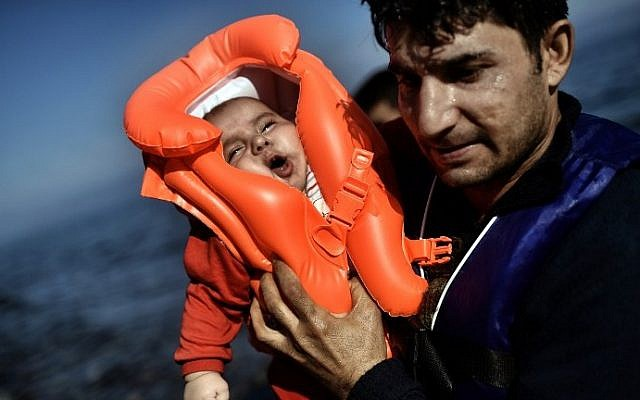 A migrant holds a baby as refugees and migrants arrive at the Greek island of Lesbos after crossing the Aegean sea from Turkey on October 5, 2015. (AFP/ ARIS MESSINIS)