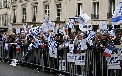 People listen to a speech by the President of the French Union of Jewish Students (UEJF) during a pro-Israel gathering outside the Israeli embassy in Paris on October 18, 2015. Placards read 'Self-defense is a right.' (AFP PHOTO/FRANCOIS GUILLOT)