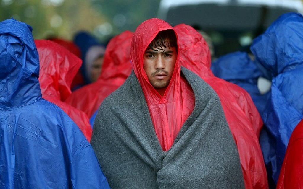 Migrants and refugees wait in the rain as they wait to enter Slovenia, at the Croatian-Slovenian border in Trnovec, on October 19, 2015. (AFP)