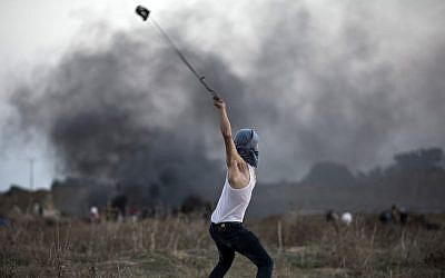 Illustrative: A Palestinian protester uses a slingshot to throw stones towards Israeli soldiers during clashes near the border fence between Israel and the central Gaza Strip on October 15, 2015 (Mohammed Abed/AFP)