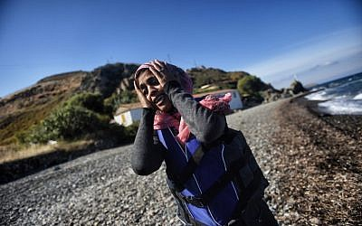 A woman reacts after arriving at the Greek island of Lesbos after crossing the Aegean Sea from Turkey on October 1, 2015. (AFP/Aris Messinis)