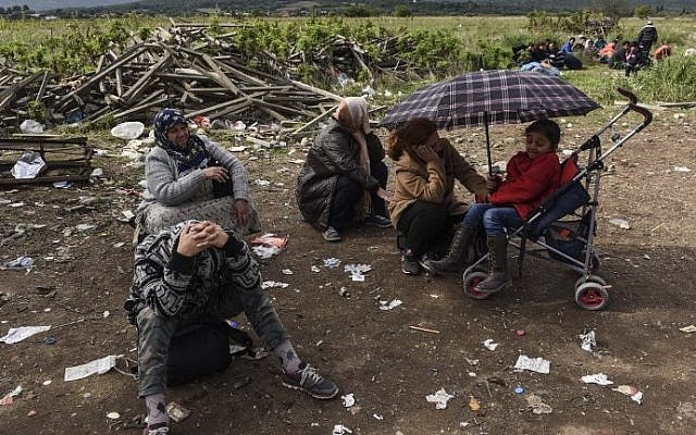 Migrants and asylum seekers rest after crossing the Greek-Macedonian border near Gevgelija, on October 2, 2015. (AFP/ ARMEND NIMANI)