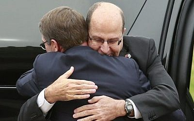 US Defense Secretary Ashton Carter embraces Defense Minister Moshe Ya'alon, facing forward, at the National Defense University in Washington, DC on October 27, 2015. (AFP/YURI GRIPAS)