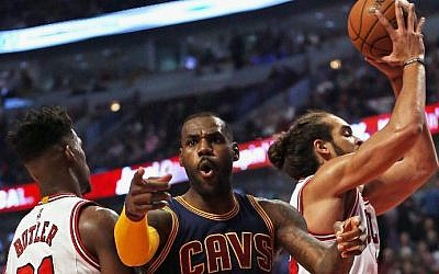 LeBron James of the Cleveland Cavaliers complains to a referee as he is trapped between Jimmy Butler and Joakim Noah of the Chicago Bulls during the season opening game at the United Center on October 27, 2015 in Chicago, Illinois. (Jonathan Daniel/Getty Images/AFP)
