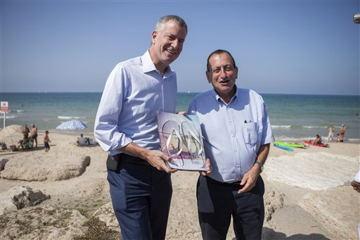 New York City Mayor Bill de Blasio, left, receives a gift from Tel Aviv counterpart Ron Huldai during their meeting in the coastal town on Saturday, Oct. 17, 2015. (AP Photo/Dan Balilty)