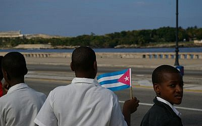 A boy waving a Cuban flag at a military parade in 2006. (CC BY Thomassin Mickaël, Flickr)