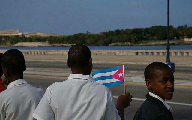 A boy waving a Cuban flag at a military parade in 2006. (CC BY Thomassin Mickaël, Flickr)