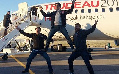 Canadian Liberal leader Justin Trudeau, center, clowns around with campaign team members Tommy Desfosses, left, and Adam Scotti after landing in Montreal, Monday, Oct. 19, 2015. (Andy Blatchford/The Canadian Press via AP)
