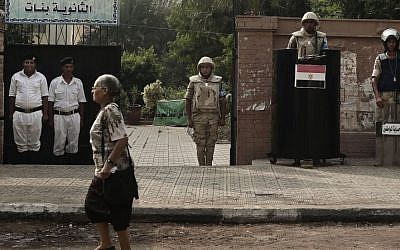 File: An Egyptian woman walks past the entrance of a polling center being guarded by army and police forces before polls open during the first round of the parliamentary election in Giza, Cairo, Egypt, Sunday, Oct. 18, 2015. (AP/Nariman El-Mofty)