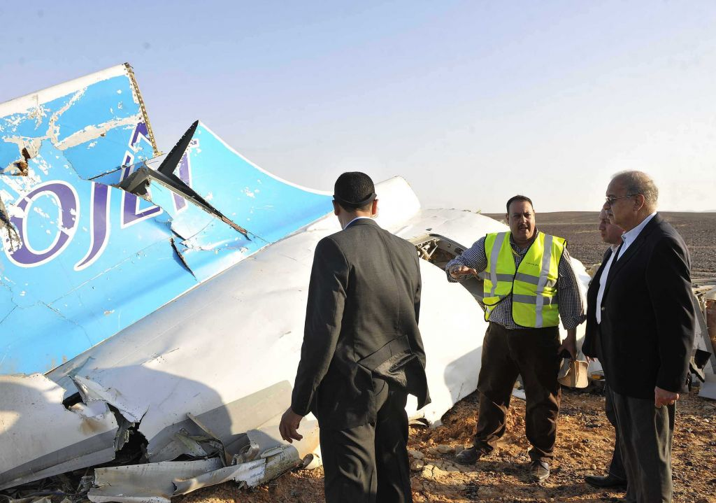 In this image released by the Prime Minister's office, Sherif Ismail, right, looks at the remains of a crashed passenger jet in Hassana Egypt, Friday, Oct. 31, 2015. A Russian aircraft carrying 224 people, including 17 children, crashed Saturday in a remote mountainous region in the Sinai Peninsula about 20 minutes after taking off from a Red Sea resort popular with Russian tourists, the Egyptian government said. There were no survivors. (Suliman el-Oteify, Egypt Prime Minister's Office via AP)