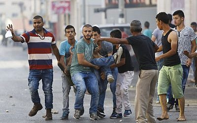 Illustrative: Palestinians carry a man who was injured in clashes with Israeli soldiers in the West Bank city of Jenin, Sunday, Oct. 4, 2015. (AP Photo/Majdi Mohammed)