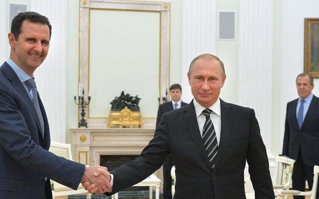 Russian President Vladimir Putin (center), shakes hands with Syrian President Bashar Assad as Russian Foreign Minister Sergey Lavrov (right), looks on in the Kremlin in Moscow, Russia, October 20, 2015. (Alexei Druzhinin, RIA-Novosti/Kremlin Pool Photo via AP)