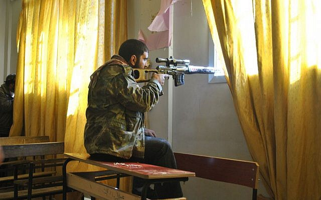 A Syrian rebel aims his rifle from inside a classroom at a school in the town of Deir Baalbeh in Homs province, Syria, February 22, 2012. (AP, File)