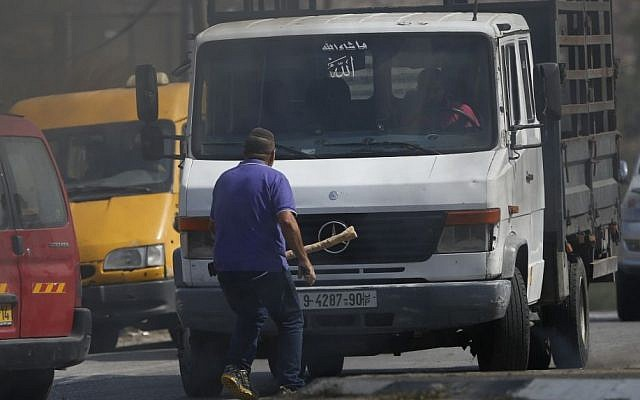 Avraham Hasano carries a large stick and walks toward an approaching truck driven by a Palestinian man at Fawar junction near the West Bank city of Hebron on Tuesday, October 20, 2015. Hasano had gotten out from his car after it was it by Palestinian stone throwers. He was run over by the truck and later died (AP Photo/Nasser Shiyoukhi)