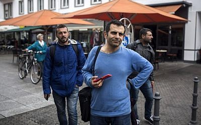 In this Sept. 16, 2015, photo, Osman al-Haj Osman, center, walks across a street in Saarlouis, Germany, with his friends Mohammed al-Haj, left, and Dr. Ahmed Naasan, who recently arrived from Aleppo, Syria. (Santi Palacios/AP)
