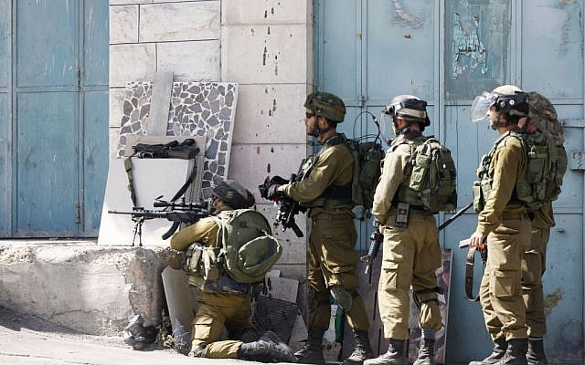 Illustrative: IDF soldiers stand with their weapons during clashes with Palestinian demonstrators in the West Bank city of Hebron, on Tuesday, October 13, 2015. (AP Photo/Nasser Shiyoukhi)