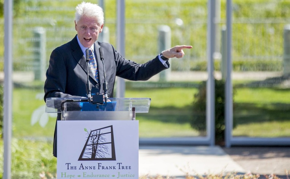 Former US president Bill Clinton speaks at the grand opening of an installation outside his presidential library honoring Anne Frank, Oct. 2, 2015, in Little Rock, Arkansas. The installation features a sapling from a tree outside the building where she and her family hid from the Nazis during World War II. (AP Photo/Gareth Patterson)