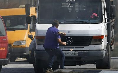 Avraham Hasano swings a large stick at an approaching truck driven by a Palestinian man at Fawar junction near the West Bank city of Hebron on Tuesday, October 20, 2015. Hasano had gotten out from his car after it was it by Palestinian stone throwers, He was run over by the truck and later died (AP Photo/Nasser Shiyoukhi)