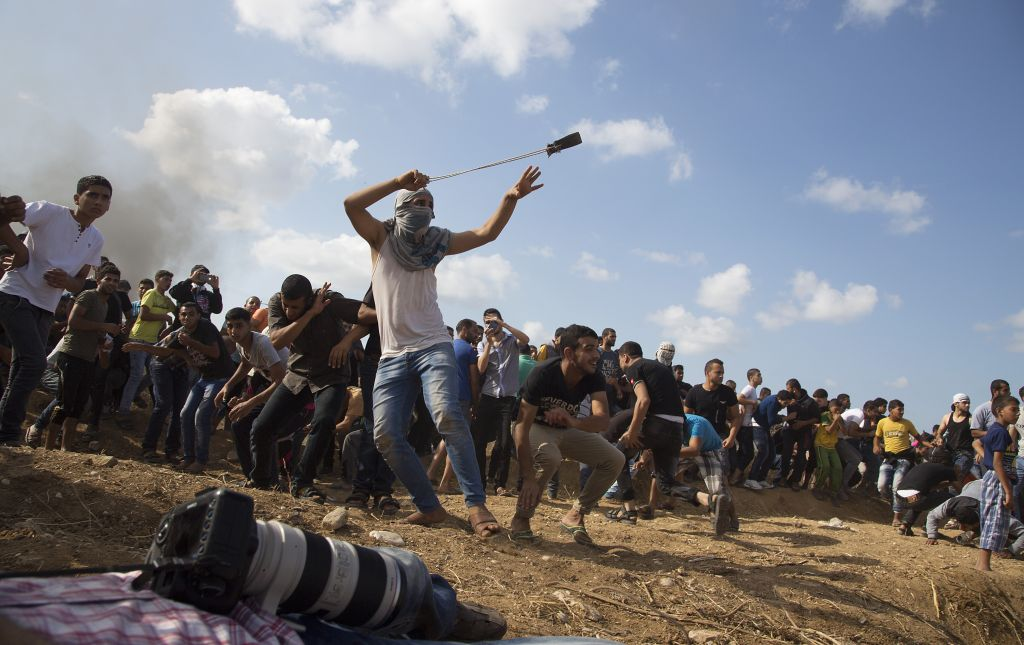 A Palestinian protester hurls stones at Israeli soldiers during clashes on the Israeli border in eastern Gaza City, Friday, Oct. 9, 2015. (AP Photo/Adel Hana)