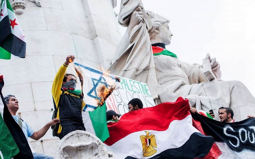 A pro-Palestinian protester displays a burning Israeli flag during a demonstration at the Place de la Republique in Paris, France, Saturday, July 26, 2014.  (AP Photo/Benjamin Girette)