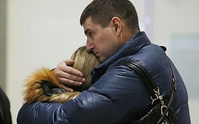 Relatives react after a Russian airliner with 217 passengers and seven crew aboard crashed, as people gather at Russian airline Kogalymavia's information desk at Pulkovo airport in St. Petersburg, Russia, Saturday, Oct. 31, 2015. (AP Photo/Dmitry Lovetsky)